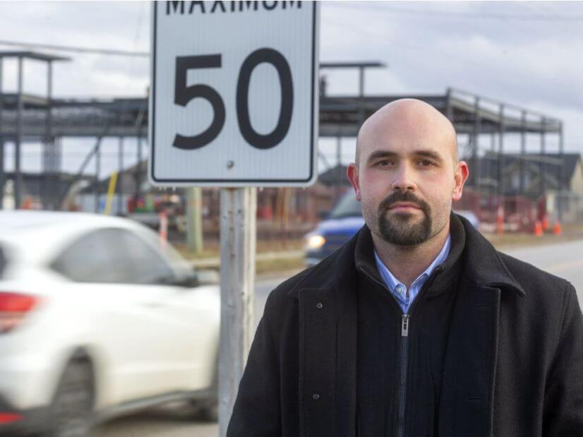 Derek Silva standing in front of a speed limit sign.